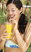Junge Frau im Bikini trinkt Orangensaft