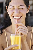 Young woman drinking orange juice through a straw