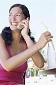 Junge Frau mit Handy und Limonade am Strandcafe