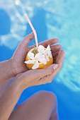 Hands holding orange with straw by pool