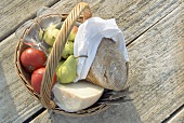 Basket with tomatoes, pears, cheese, bread and glasses