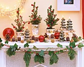 Kaminsims mit Zuckerhutfichten, Kerzen und Girlande