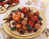 Teller mit Äpfeln, Nüssen, Sternanis und Zimtstangen