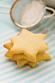 Four star-shaped biscuits in a pile with icing sugar