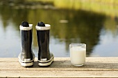 Child's wellies and glass of milk on a landing stage