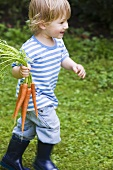 Boy running with carrots in his hand