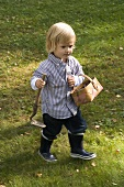 Boy carrying hand hoe tool and small basket
