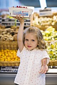 Small girl holding up a punnet of redcurrants in a supermarket