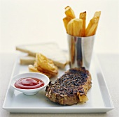 Peppered steak with chips, ketchup and sliced bread