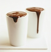 Overflowing chocolate sauce in white pots