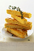 Cheese fingers with thyme, in a pile on plate