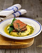 Roast beef with herb butter on polenta