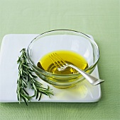 Olive oil in small glass bowl with fork, rosemary beside it