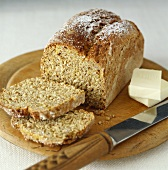 Wholemeal bread (slices cut) and butter on wooden plate