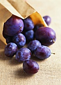 Plums in and in front of paper bag