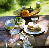 Bean salad with soft cheese and white bread on table in garden