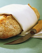 Bread with white tea towel and knife
