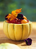 Melon filled with summer fruit and flowers