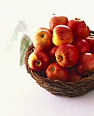 Red apples in wicker basket on white background