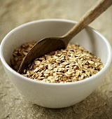 Rolled oats in white bowl with wooden spoon