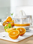 Fresh orange halves in front of electric juicer