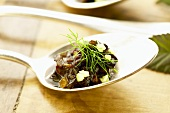 Lamb kidneys with balsamic vinegar and celery on spoon