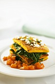 Polenta slices with spinach, diced tomato and pine nuts