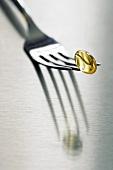 Yellow vitamin capsule on fork