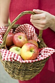 Woman holding a basket of fresh apples