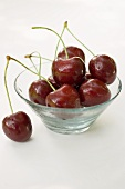 Cherries with drops of water in glass bowl