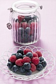Blueberries and raspberries on plate and in storage jar