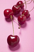 Several cherries on pink background