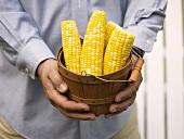 Man holding woodchip basket full of corn cobs