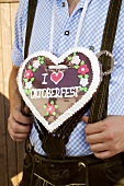 Man in national dress with Lebkuchen heart (Oktoberfest, Munich)