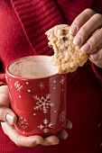 Hands holding cranberry biscuit and coffee mug