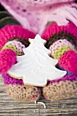 Child's hands in woollen mittens holding gingerbread fir tree