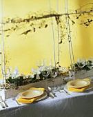 Gedeckter Tisch in den Farben Weiss und Gelb zu Weihnachten