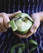 Hands peeling a green apple