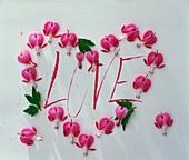 Herz aus rosa Blüten (Tränendes Herz) mit Schriftzug Love