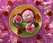 Carnations, ranunculi & gypsophila in red heart-shaped bowl