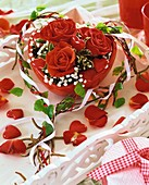 Red roses and gypsophila in red heart-shaped bowl