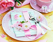Place-setting with pink Bellis, fabric napkin and ribbon