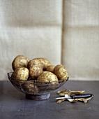 Potatoes in a wire basket, potato peelings beside it