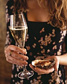 Woman holding oyster with chilli ginger sauce & glass of champagne