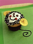 Cupcake with amusing face and banana chips for children