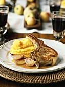 A pork chop with shallots and mashed potatoes