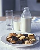 Assorted biscuits on plate, milk in bottle and glass