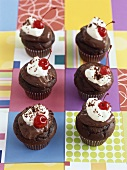 Chocolate muffins with chocolate icing, cream and cherries