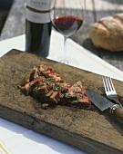 Beef steak, sliced, on chopping board