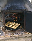 Several calzone on baking tray in wood oven